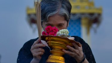 A Thai mourner prays in front of a replica of the royal crematorium in Bangkok.