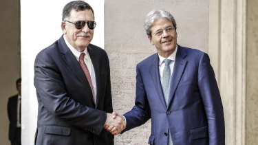 Italian Premier Paolo Gentiloni, right, welcomes Libyan Prime Minister Fayez al-Sarraj in the courtyard of Chigi Palace in Rome.