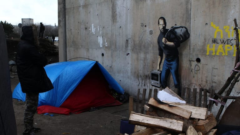 Street artist Banksy has highlighted the migrant crisis in a mural at a refugee camp in France.