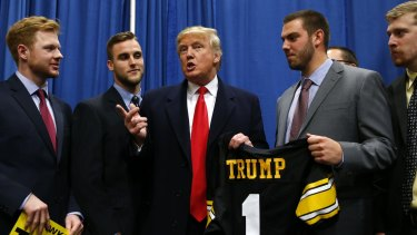 Republican presidential candidate Donald Trump speaks with University of Iowa football players before a campaign event at the University of Iowa.