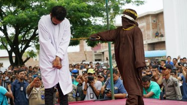 A man is whipped in public for violating sharia law in relation to homosexuality in Banda Aceh, Indonesia.
