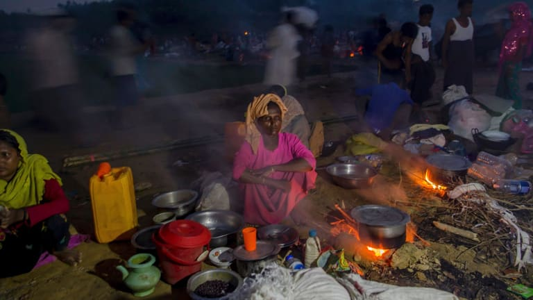 Rohingya Muslims, who crossed over from Myanmar into Bangladesh, prepare a meal in the open at Taiy Khali refugee camp, in Bangladesh.