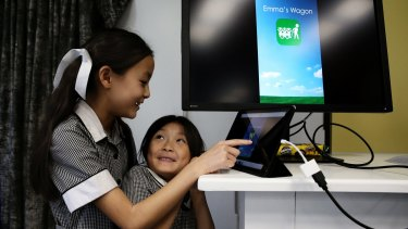 Emma Yap showing her younger sister Hannah the app she created, Emma's Wagon.