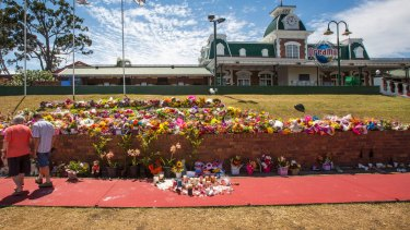 Floral tributes outside Dreamworld where the deaths of four people have raised questions about workplace laws in Queensland and prompted a safety review of the state's theme parks.