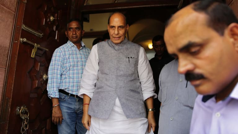Indian Home Minister Rajnath Singh, centre, comes out from parliament house after making a statement on the attacks on four men beaten while trying to skin a dead cow.