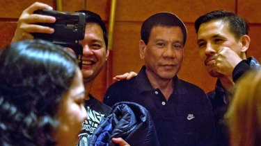 Will the real Duterte stand up?: Members of the Filipino community in China pose with a cut-out of their president. His ultimate goals on foreign policy remain unclear.