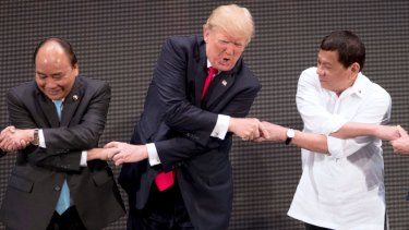 """US President Donald Trump, center, reacts as he does the """"ASEAN-way handshake"""" with Vietnamese President Tran Dai Quang, left, and Philippines President Rodrigo Duterte during the opening ceremony of the ASEAN summit in Manila, Philippines."""