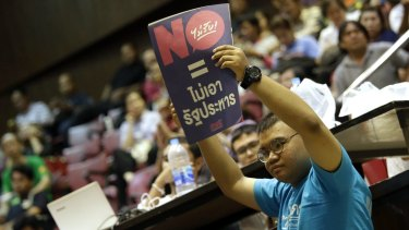 """A student holds a poster reading """"vote no = no coup """" at Thammasat University in Bangkok on Sunday."""