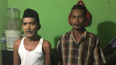 Syaiful, right, the son of murder victim and suspected sorcerer Enja, with his father, Atmadin.