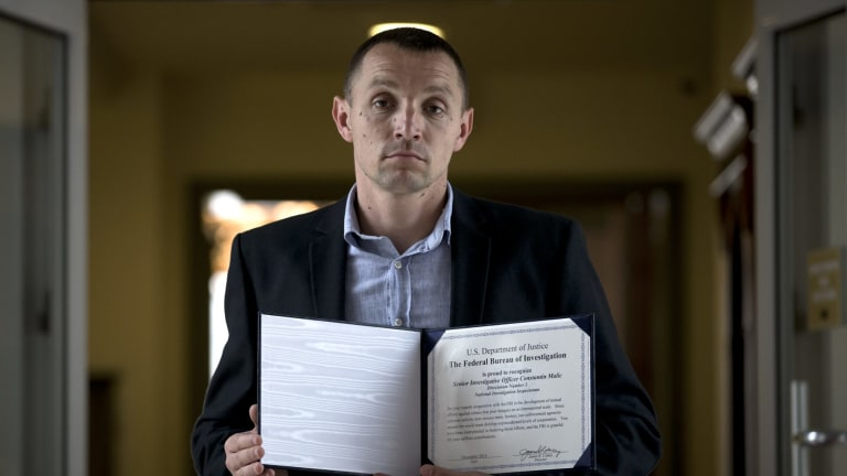Former Moldovan police investigator Constantin Malic holds an award received from the FBI in Chisinau, Moldova. By the time of the award ceremony, his team had been disbanded.