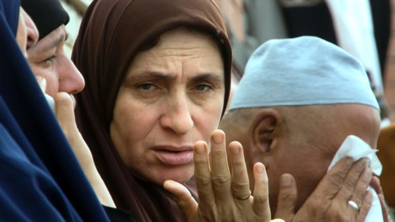 Relatives of injured worshippers grieve outside the hospital.