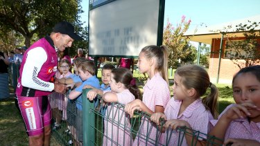 Students at St Joseph's Primary School welcome former Prime Minister Tony Abbott as he arrives in Eugowra during the 2016 Pollie Pedal tour.
