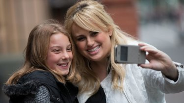Hollywood actress Rebel Wilson poses with a young fan outside Melbourne's Supreme Court earlier this month.