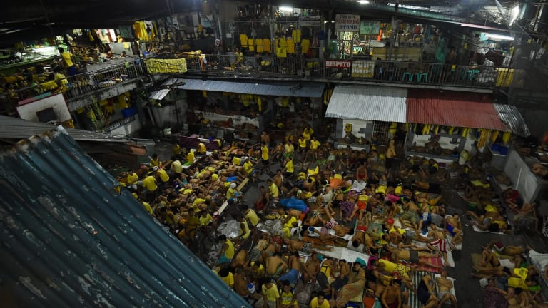 Some of the 3562 inmates sleep on any available space on the basketball court in jail in Manila, Philippines. The congestion is due to the war on drugs.