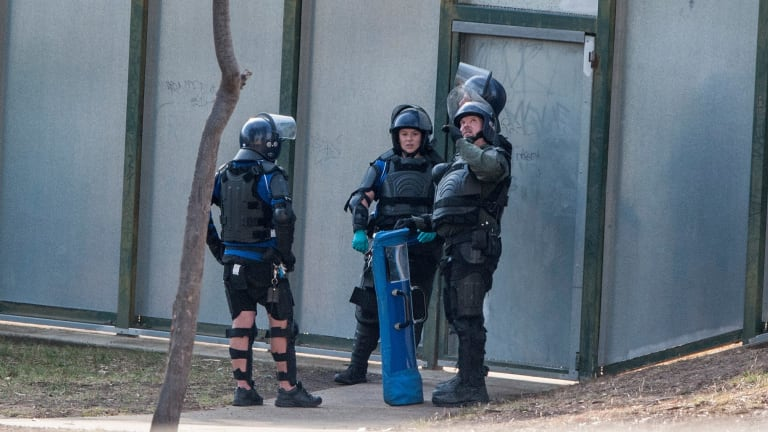 Heavily armed riot police monitor six youths who were on the roof of the Melbourne Youth Justice Centre in Parkville in March.