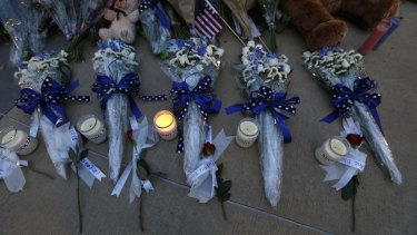 Candles and flowers placed in honor of slain Dallas police officers in front of police headquarters, in Dallas.
