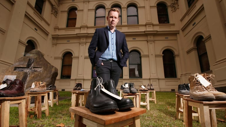 Victorian Trades Hall Council Secretary Luke Hilakari poses among the work boots symbolising workers killed on the job in the past 12 months.