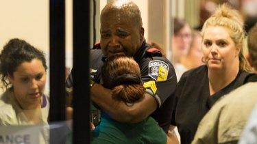 A Dallas Area Rapid Transit police officer receives comfort at the Baylor University Hospital emergency room entrance.