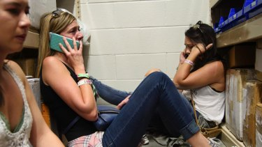 Women make phone calls while taking shelter inside the Sands Corporation plane hangar after the mass shooting in Las Vegas.