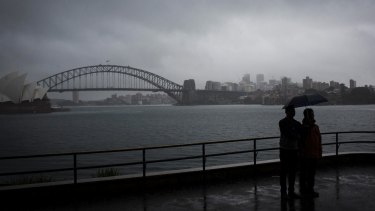 Tourists huddle under an umbrella as rain hits Sydney on Wednesday.