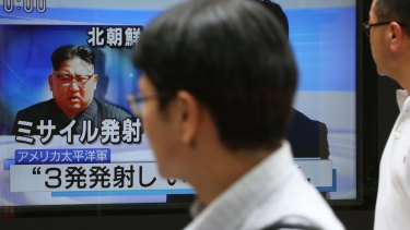 Passers-by watch a TV news program showing image of North Korean leader Kim Jong-un, in Tokyo.