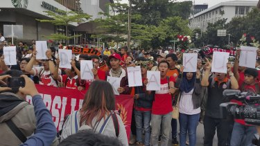 """Jakarta Football Club supporters sing while holding letters saying """"kami tidak takut"""" (We are not afraid) at a vigil at the site of the Jakarta terror attack."""