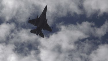 A Jordanian fighter jet flies overhead as King Abdullah II visits the family of slain pilot Muath al-Kasasbeh.