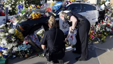 Dallas police Sergeants Amanda Renteria, left, and Laura Browning lay flowers and candles outside a Dallas Police Department.