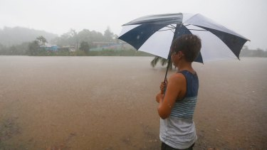 A young boy looks out over the swollen Tweed River in Murwillumbah after heavy rain.