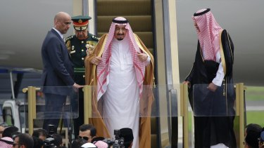 Saudi King Salman adjusts his headscarf as he steps off the escalator from his personal jet in Jakarta.