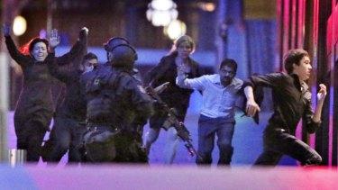 Hostages flee from the Lindt cafe.