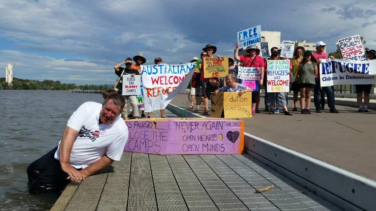Protesters in Canberra launching cardboard boats in Lake Burley Griffin calling for an end to offshore processing in Manus Island and Nauru.