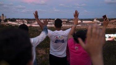 People pray for peace toward the Alcacuz prison in Nisia Floresta, near Natal, Brazil.