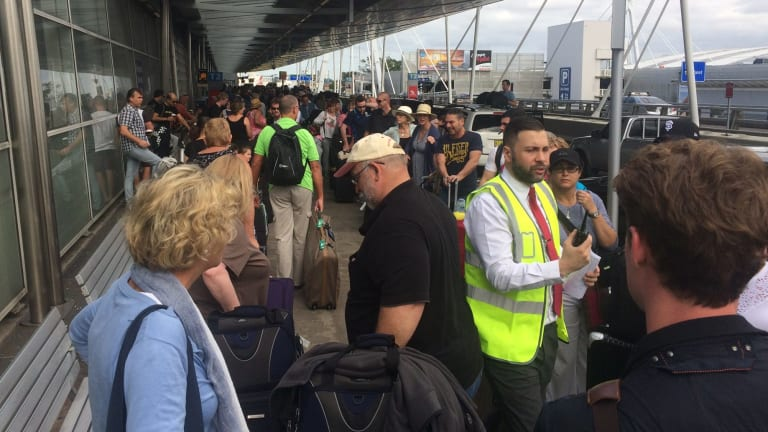Passenger queue for Virgin Australia snakes outside the domestic terminal at Sydney Airport.