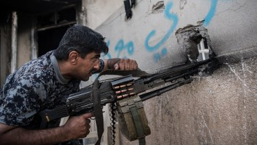 An Iraqi federal policeman fires a machine gun at an Islamic State position during the battle to recapture west Mosul .
