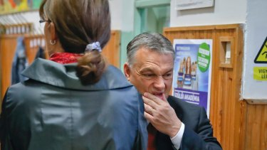 Hungarian Prime Minister Viktor Orban pauses after voting in the referendum with his wife Aniko Levai.