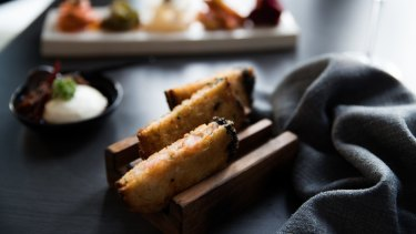 Prawn toasts are cutely served in wooden toast racks.