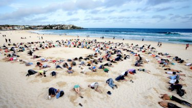 Protesters bury their heads in the sand at Bondi Beach to send a climate change message to Tony Abbott during the G20 Summit in Brisbane.