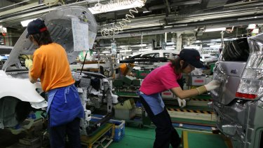 Workers assemble Toyota Prius hybrid vehicles on the production line of the company's Tsutsumi plant in Toyota City in Japan.