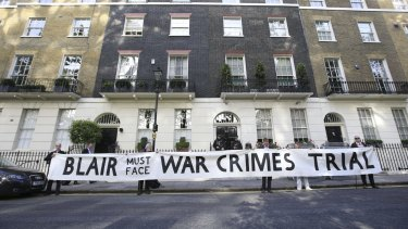Protesters hold a banner outside the London home of Tony Blair.