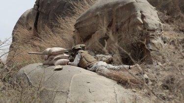 A Saudi soldier aims a machine-gun from behind a sandbag barricade on the border with Yemen in Jazan, Saudi Arabia, in April.