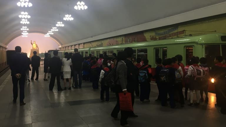 School children in the underground, as a gold statue of Kim Il-sung towers over commuters.