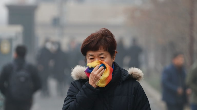 A woman uses a scarf to cover her for protection against air pollution walks on street in Beijing.
