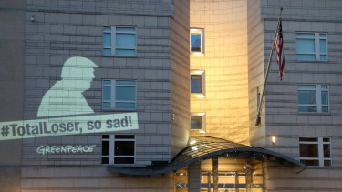A Greenpeace banner showing US President Donald Trump and the slogan '#TotalLoser, so sad!' is projected on the facade of the US Embassy in Berlin, Germany.