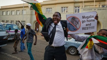 Zimbabweans celebrate outside the parliament building immediately after hearing the news that President Robert Mugabe had resigned, in downtown Harare, Zimbabwe.
