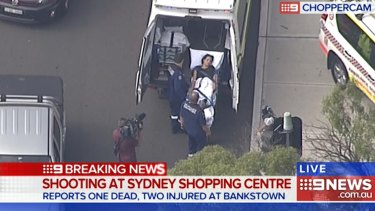 A victim is loaded into an ambulance after a shooting at Bankstown Central Shopping Centre.