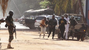 Hostages flee the Radisson Blu hotel in Mali. The man in the black suit is reportedly Guinean singer Sekouba Bambino, who escaped.