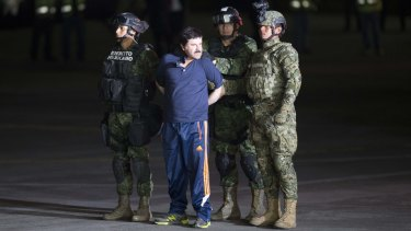 "Joaquin ""El Chapo"" Guzman is made to face the press as he is escorted to a helicopter in handcuffs by Mexican soldiers and marines."