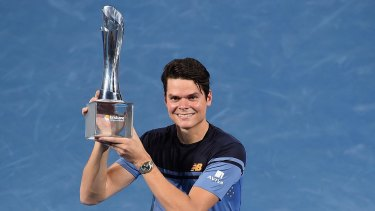 Milos Raonic of Canada holds the Roy Emerson trophy after winning the Brisbane International.