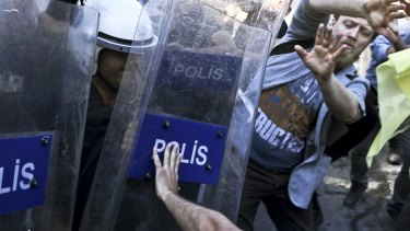 Turkish riot police push to disperse anti-goverment protestors at the Gay Pride parade.